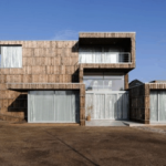 House façade covered with recycled boards from wooden spools