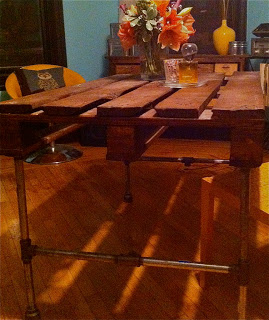 Build a table with a wooden pallet and some stainless steel pipes